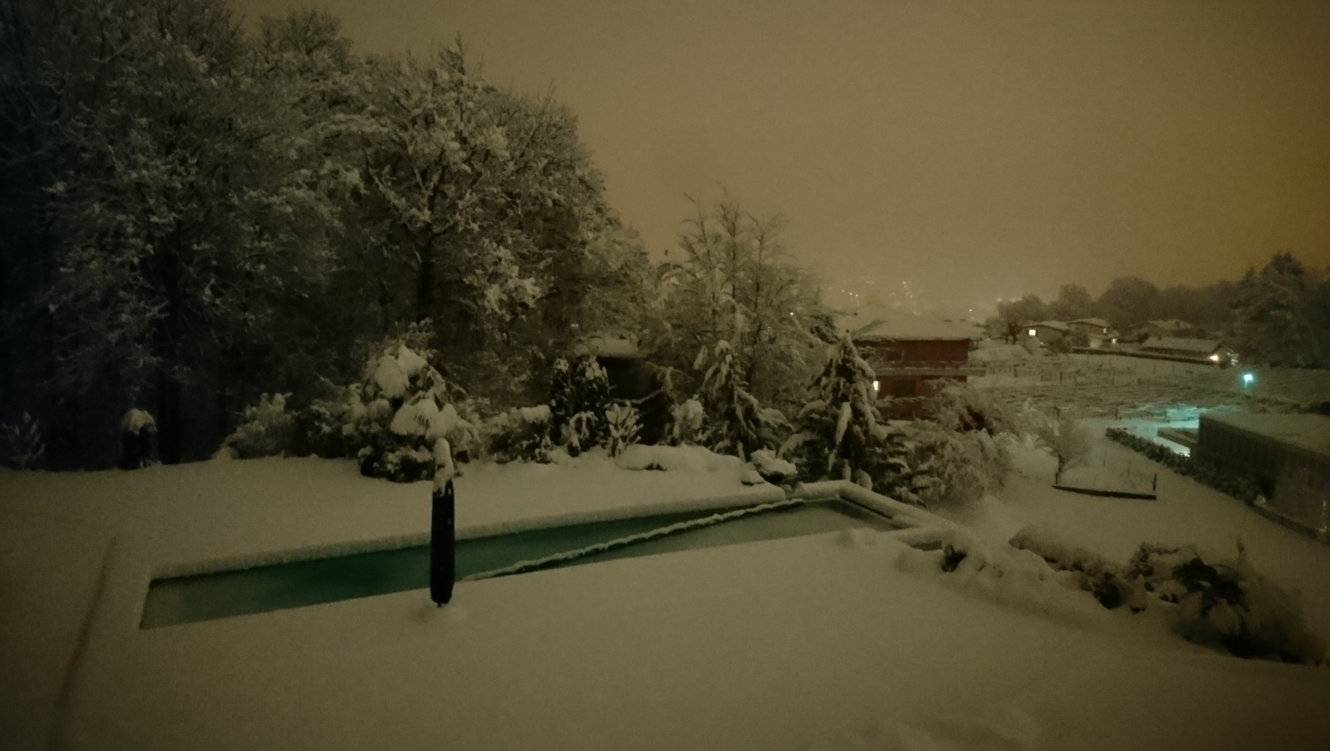 Garden with pool and umbrella: everything covered by snow. Night time picture.